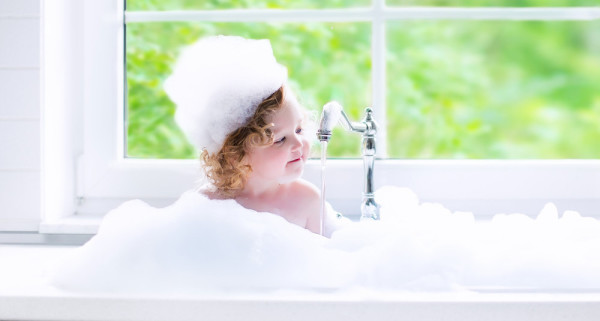 Baby girl taking bath with foam